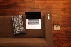 Laptop on red couch with slippers and remote
